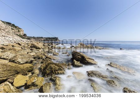 Rocky Palos Verdes Estates coast with motion blur waves in Los Angeles County, California.