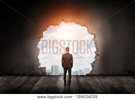 A businessman watches clear blue sky through a big uneven hole in a concrete wall. Business growth. Booming industry. New business projects.