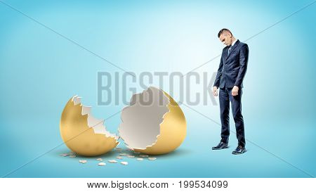 A sad businessman on blue background looks down on a giant broken golden egg. Loss of income. Financial trouble. Riches to rags.