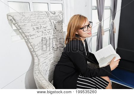 Business woman sitting at chair and reading red book in her room Charming girl in uniform and glasses concept of business learning business and education.