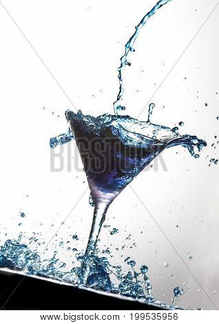 Blue cocktail being poured into martini glass