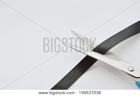 scissors blade cutting black cloth ribbon on white background
