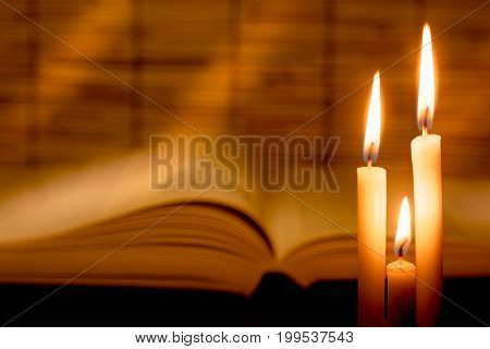 Close-up View Of Old Burning Candle With Blurred Old Book On Wooden Background.   Education Concept