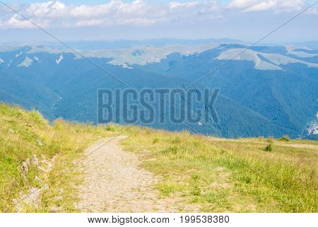 A tracking path over the mountain at Carpatians and beautiful blue sky at the background Bucegi natural park near Sinaia Romania on sunny summer day.