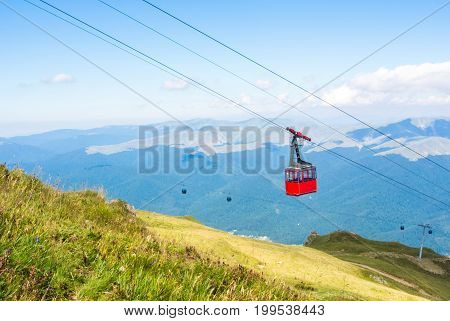 A View To Red Open Cableway Cabin Over The Top Of The Mountain And Beautiful Landscapes With Blue Mo