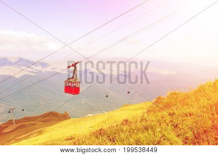 A Toned View To Bright Red Cableway Cabin Moving To The Top Of The Mountain Over The Beautiful Lands