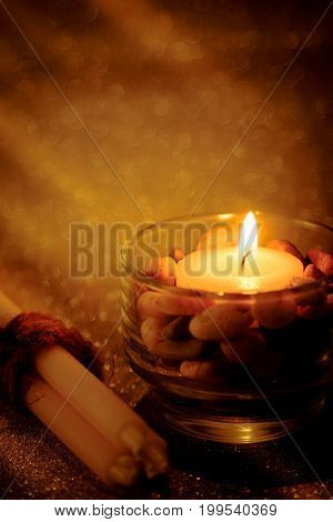 Abstract background for pray or meditation caption. Still life golden candle light with reflection on golden blurred bokeh background.