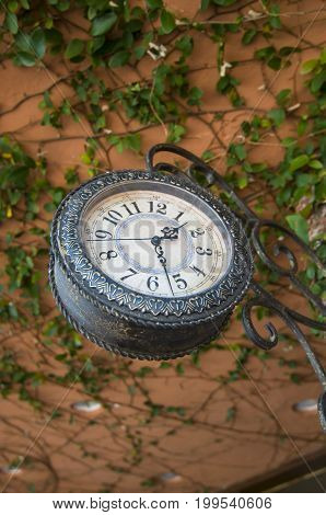 Hanging antique clock in front of a store