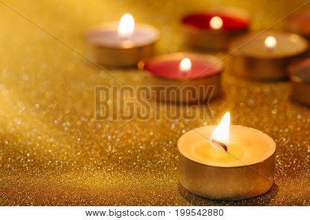 Prayer and hope concept. Retro candle light with lighting effect and glitter abstract background with bokeh defocused lights.