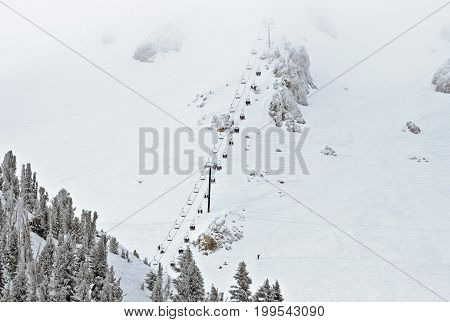 Ski lift chair ascending the mountainside of a ski resort