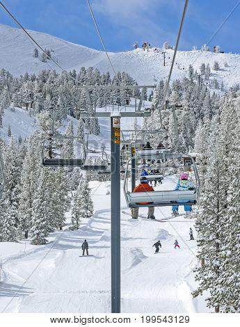 Winter ski lift riders on mountain runs