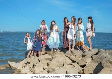 summer holidays and vacation - hippie girls with drinks on the beach