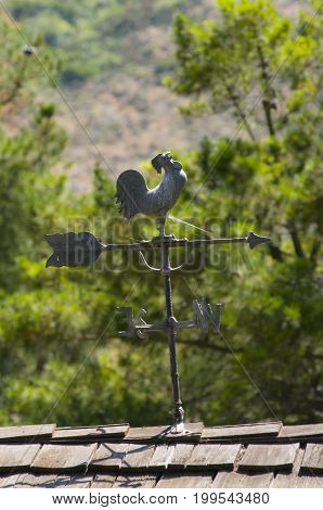 rooster weather vane attached to roof of a house