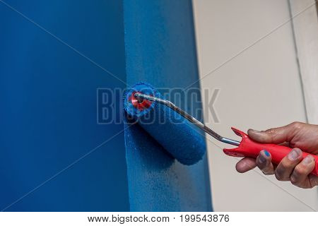 Decorator's hand painting wall with roller in home