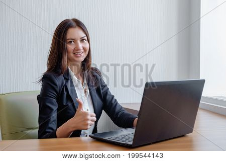 beautiful smiling business woman working on laptop and shoving thumbs up