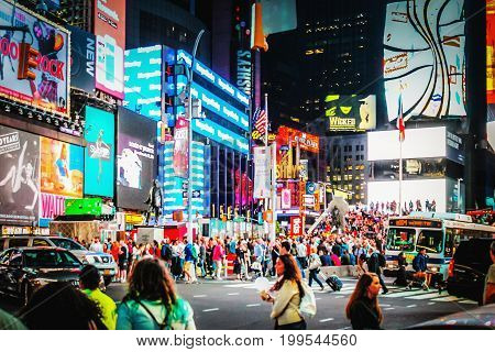 New York USA - 26 September 2016: Massive advertising Billboards tower above traffic and pedestrians at the intersection between Times Square and Broadway.