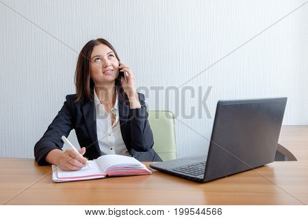 young business woman with notebook, calendar and mobile phone at work.