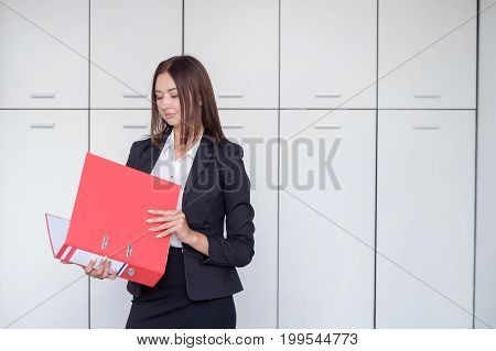 Young happy businesswoman holding red folder and posing for portrait on office