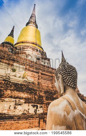 Selective Focus Image Of Ancient Buddha Statue With Old Big Pagoda Background In Wat Yai Chai Mongko