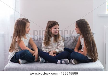 Portrait of three happy girls sitting on sofa and friendship concept.