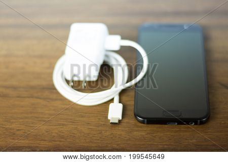 New fast USB Type-C port mobile phone and cable on wooden background