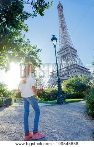 Beautiful girl in Paris with Eiffel tower on background.