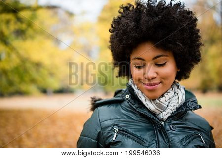 Teenage girl outdoors in autumn, looking down.