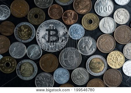 Silver bincoin with international money coins new currency among old currencies business and finance concept on black stone table background