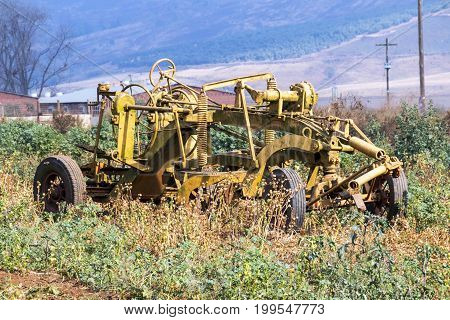 Vintage yellow farm implement against rural farm landscape in South Africa