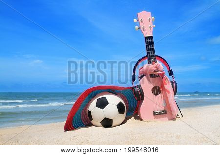 pink headphones ukulele and handcraft hat football on blue sky and beach background