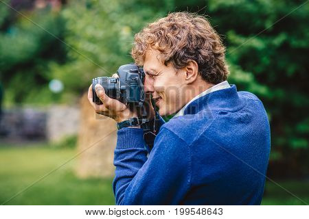 A Smiling Man With A Camera. A Photographer Takes Pictures Outdoors. Close-up Portrait Of The Photog