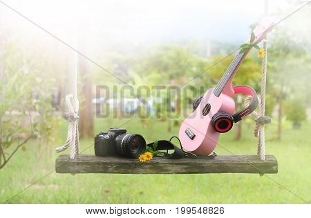 sweet pinkheadphones ukulele music camera on wooden swing and green grass background.