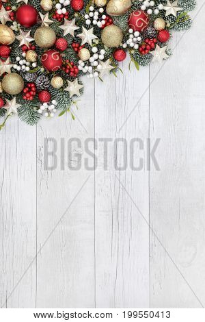 Christmas background border with red, gold and white bauble decorations, holly, mistletoe and fir on rustic white wood background.