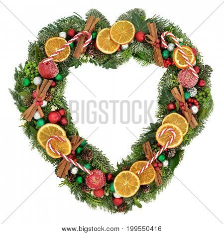 Heart shaped mistletoe wreath with dried orange fruit, apples, cinnamon sticks, candy canes, bauble decorations, holly and winter greenery  on white background.