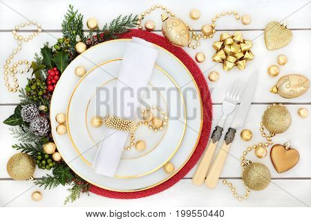 Christmas dinner place setting with porcelain plates, gold bauble decorations, holly, mistletoe, ivy and fir on rustic white wood background