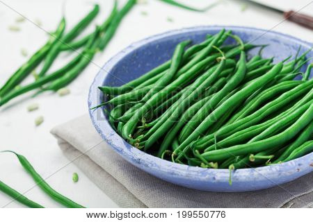 Crop of green or string beans in vintage blue bowl on white table. Organic and diet food.