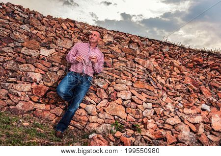 A male model with a cigar, a glass of wine, leaning against a red stone wall