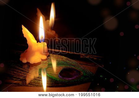 Prayer And Hope Concept . Retro Candle Light With Peacock Feather Eye. Vintage Image