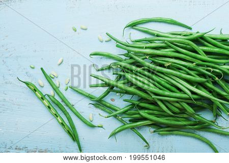 Green or string beans on blue vintage table top view. Organic and healthy food. Farmers autumn harvest.