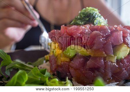 Woman piking ahi Tuna Tartar with fork. Closeup