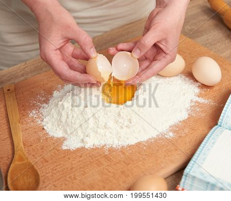 Woman preparing flour for baking on a wooden background. Kitchen utensils. Hands and food closeup. Break an egg, cooking dough.