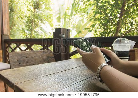 Copy space of hand hold cell phone on wooden table with nature background. business concept