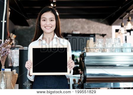 Young asian women Barista holding blank chalkboard menu with smiling face at cafe counter background small business owner food and drink industry concept