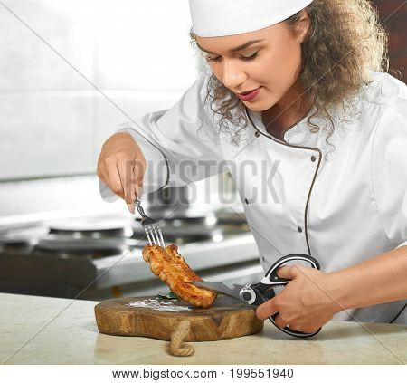 Cropped shot of a female chef preparing delicious grilled chicken steak at her kitchen cutting it with scissors copyspace restaurant food eating meat concept.