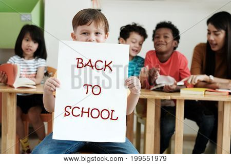 Cute boy holding back to school poster with happy face in kindergarten classroom education concept