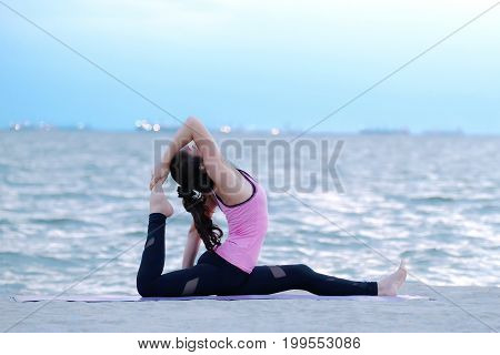 Young woman practicing yoga on beach in Pigeon pose wellness well being