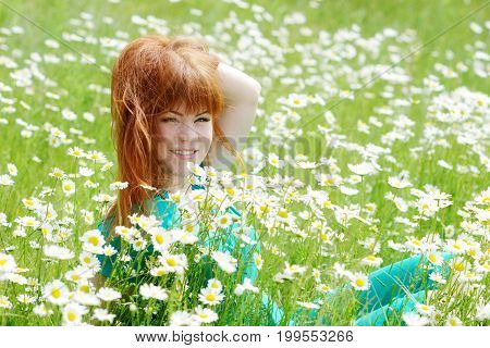redhead young woman in the field of daisies