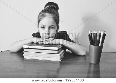 tired preschooler girl with pile of books
