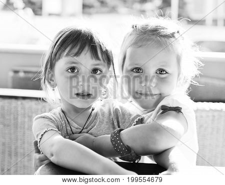 two sweet little friends sitting and hugging