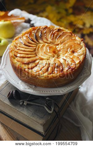 Apple tart on a background with books, apples and autumn leaves.